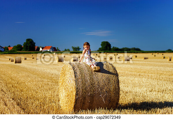Funny cute little girl posing on the haystack in summer field - csp29072349
