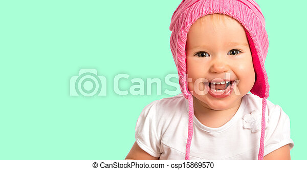 Funny happy baby girl in a pink  winter knitted hat laughing - csp15869570