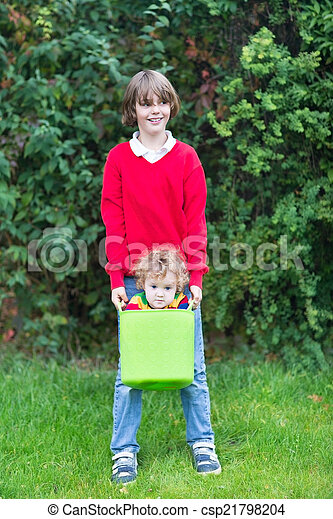Funny happy brother and baby sister playing with a laudry basket - csp21798204
