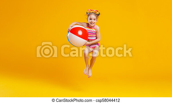 25d87c5a77 funny happy child jumping in swimsuit on colored background