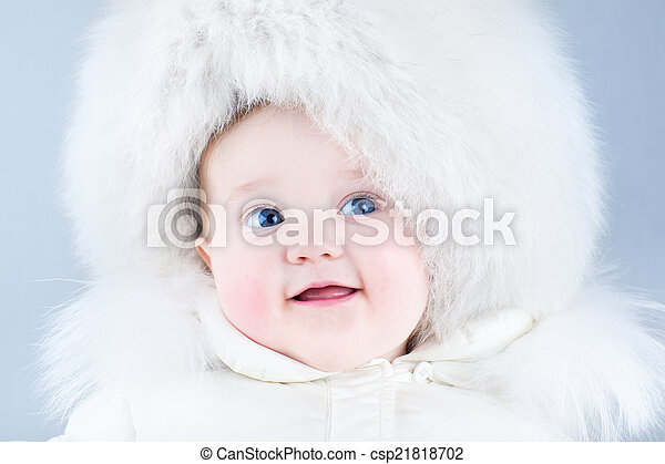 Funny laughing baby in a big white fur hat - csp21818702