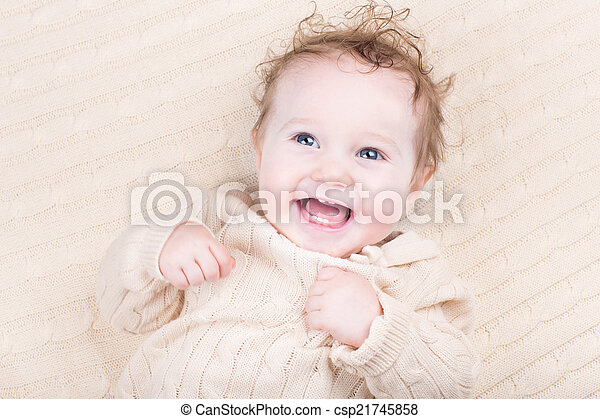 Funny laughing baby in a knitted dress - csp21745858