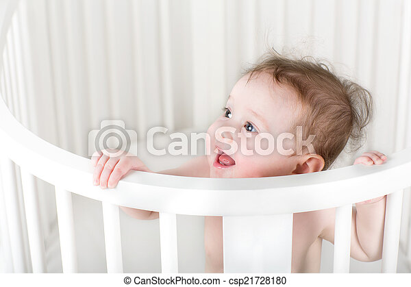 Funny little baby standing in a white round crib - csp21728180