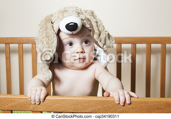 Funny little baby with beautiful standing in a round white crib - csp34190311