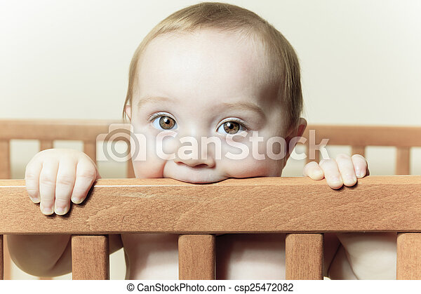Funny little baby with beautiful standing in a round white crib - csp25472082
