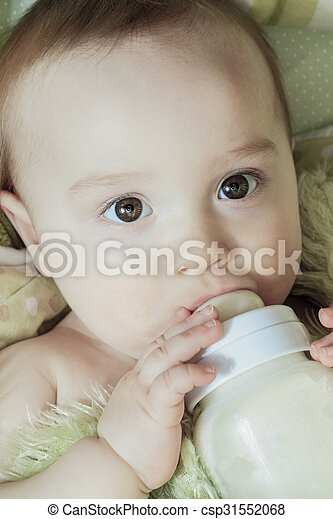 Funny little baby with beautiful standing in a round white crib - csp31552068