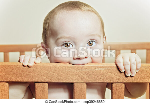 Funny little baby with beautiful standing in a round white crib - csp39246650