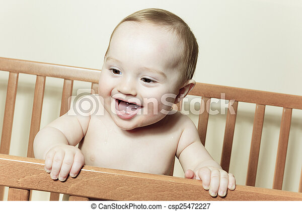 Funny little baby with beautiful standing in a round white crib - csp25472227
