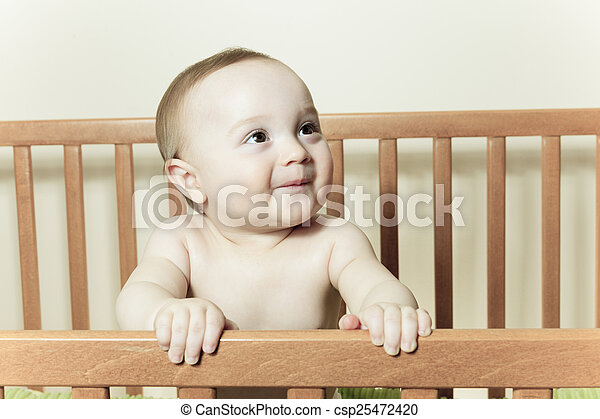 Funny little baby with beautiful standing in a round white crib - csp25472420