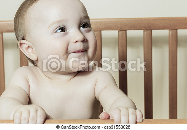 Funny little baby with beautiful standing in a round white crib - csp31553028