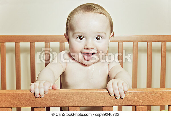 Funny little baby with beautiful standing in a round white crib - csp39246722