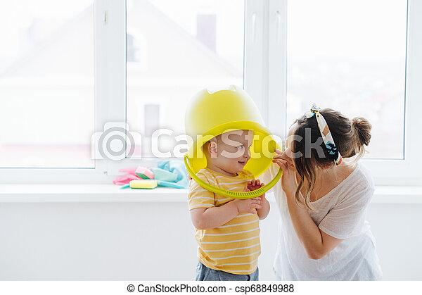 Funny little blond toddler boy is wearing big plastic bucket - csp68849988