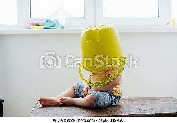 Funny little blond toddler boy is wearing big plastic bucket - csp68849950