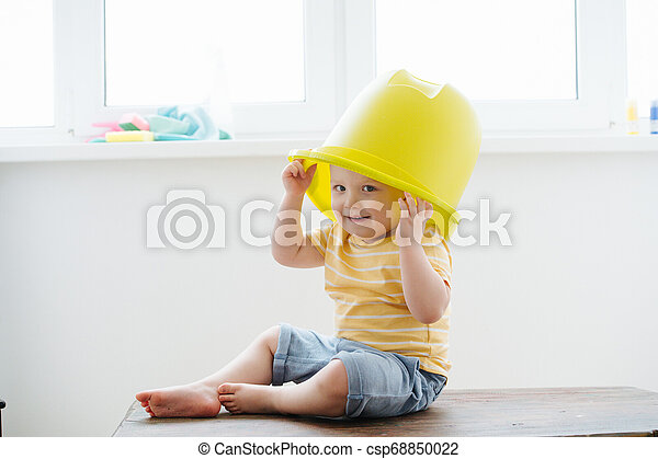 Funny little blond toddler boy is wearing big plastic bucket - csp68850022