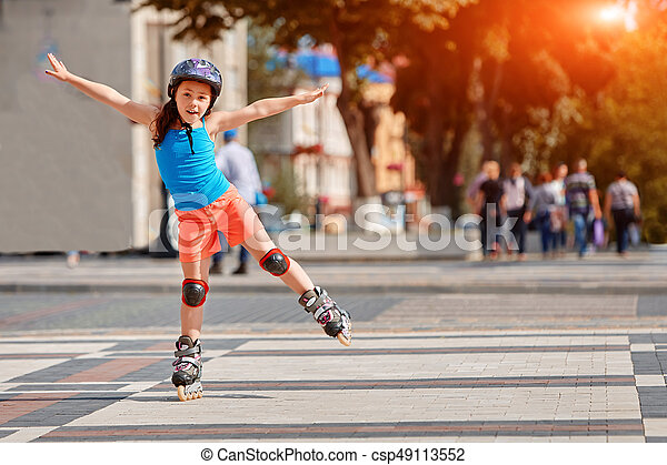 Funny Little pretty girl on roller skates in helmet riding in a park. - csp49113552