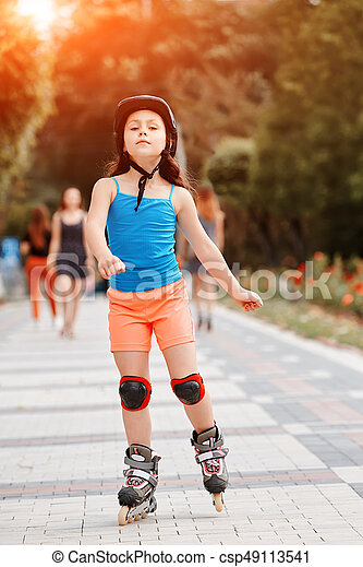 Funny Little pretty girl on roller skates in helmet riding in a park. - csp49113541