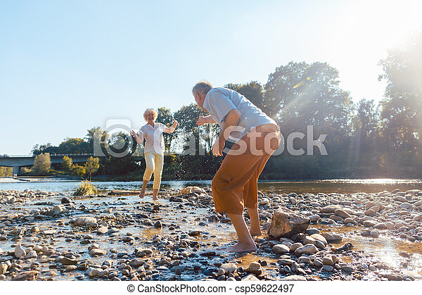 Funny senior couple playing with water at the river in a sunny day - csp59622497