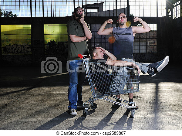 funny shopping group of three young man with shopping cart outdoor