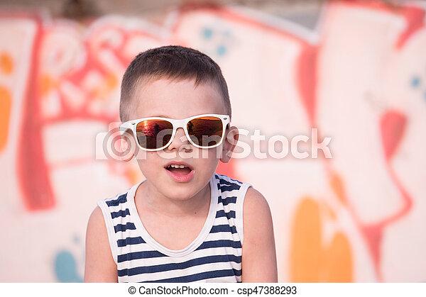 81ac7a61b9c6 Funny small kid wearing sunglasses and shirt on graffiti background ...