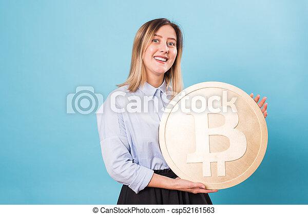 Funny woman holding a Golden Bitcoin. virtual money. - csp52161563