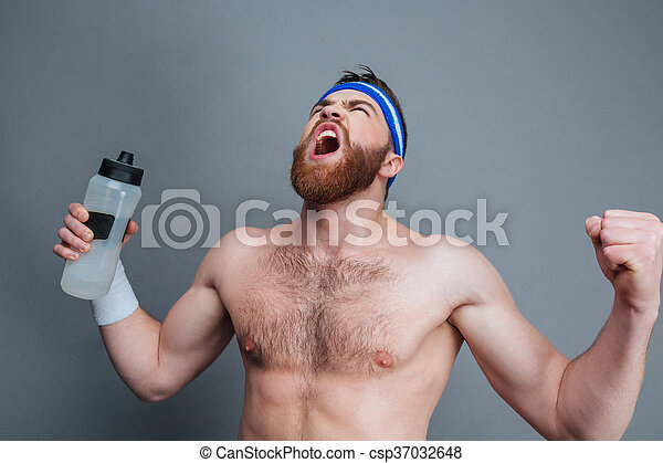 Furious bearded sportsman with bottle of water standing and shouting - csp37032648