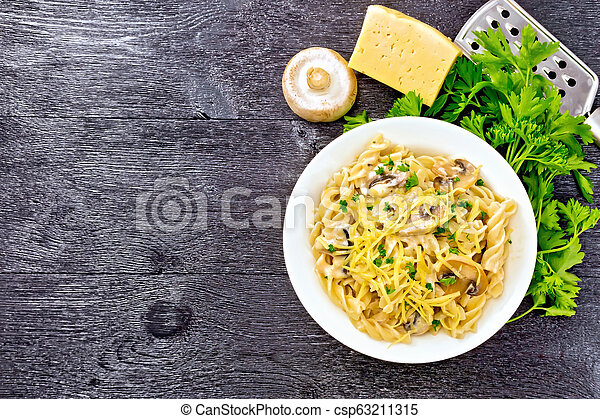 Fusilli with mushrooms in plate on board top - csp63211315