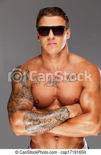 Hombre guapo con gafas de sol con el torso musculoso tatuado - csp17191659