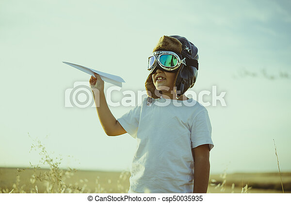 Game, Boy playing to be airplane pilot, funny guy with aviator cap and glasses, carries in his hand a plane made of paper - csp50035935