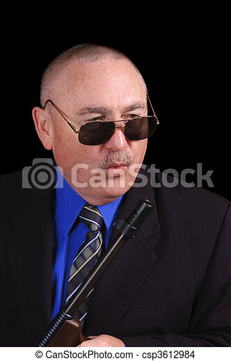 Gangster or Government agent, FBI agent, with a machine-gun over a black background - csp3612984