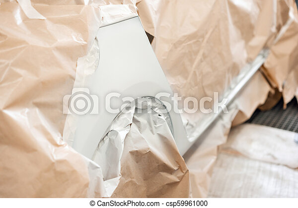 Garage painting car service  section of the car is covered with primer   vehicle is covered with protective paper  Repairing car body work after the