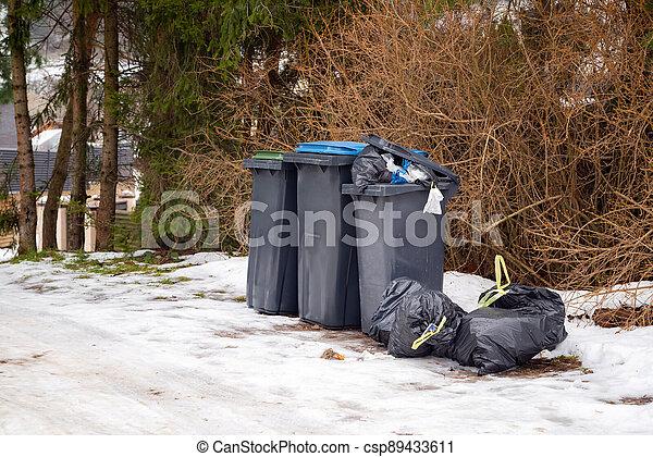 Garbage bin full of trash on white snow in residential area in winter. - csp89433611