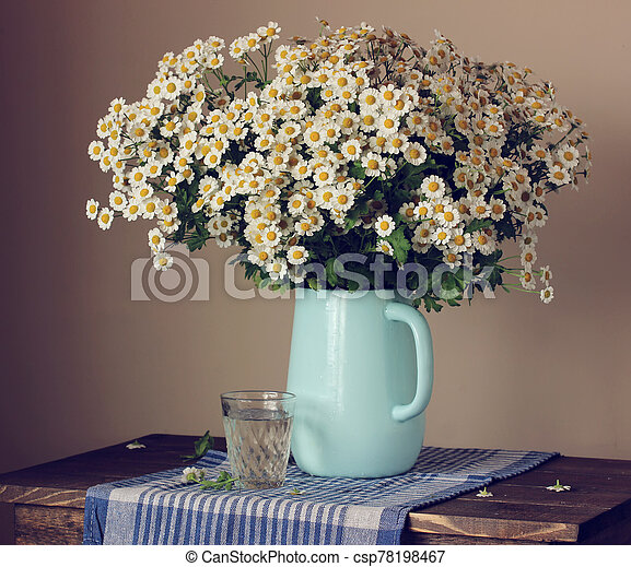 Garden daisies in a jug on the table. Still life with flowers. - csp78198467