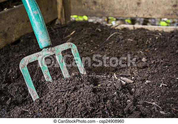 Garden fork turning compost - csp24908960