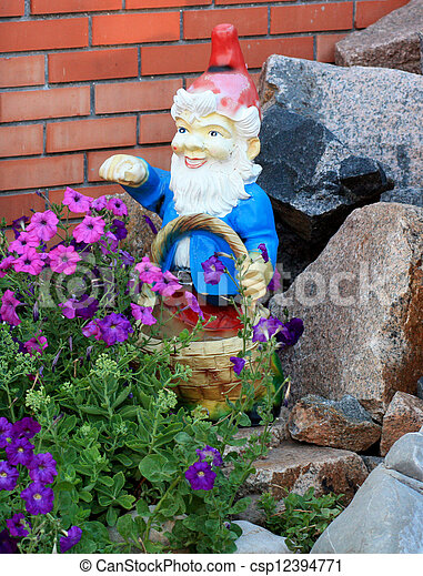 Garden gnome with a basket of flowers and stones against a brick wall