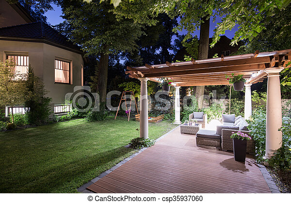 Garden with patio at night - csp35937060
