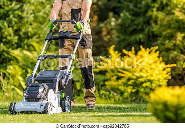 Garden Worker with Lawnmower Cutting Grass - csp92042785
