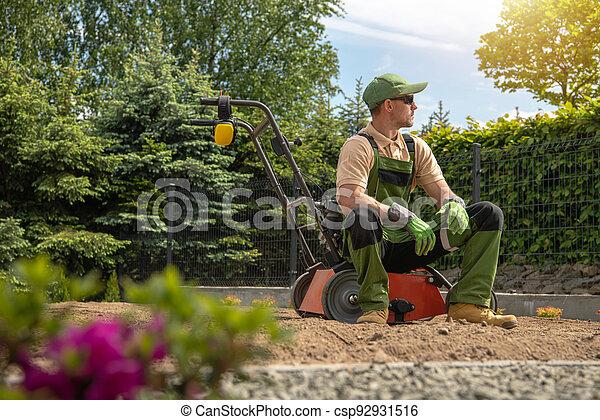 Gardener Relaxing After Backyard Lawn Aeration - csp92931516