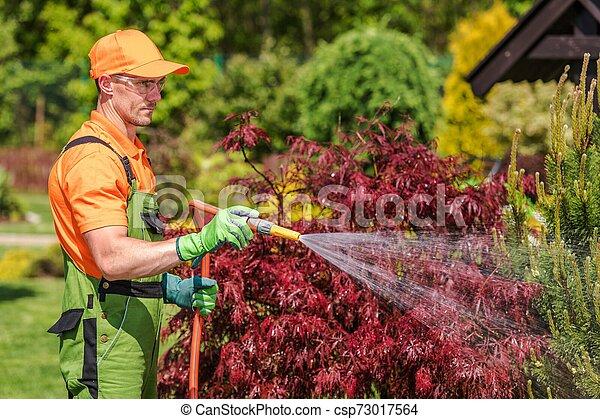 Gardener with Garden Hose - csp73017564