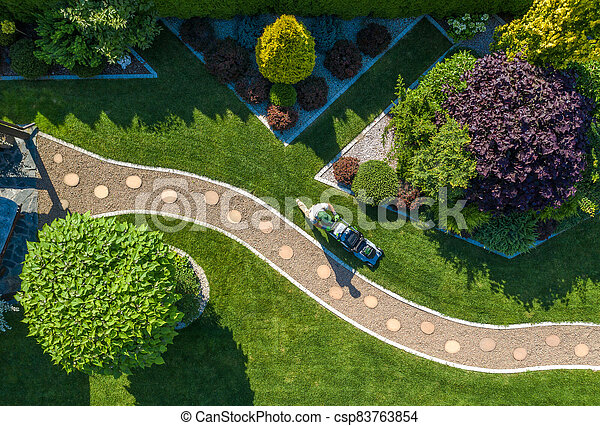 Gardener with Grass Mower Trimming Backyard Lawn Aerial View - csp83763854