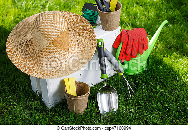 Gardening tools and a straw hat on the grass in the garden ...