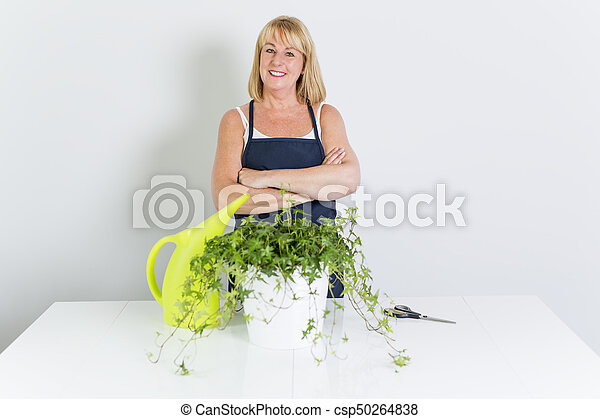 Gardening woman with plant. Isolated on white background. - csp50264838