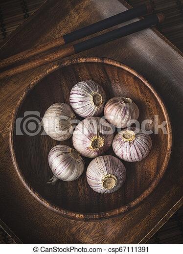 Garlic in a wooden bowl - csp67111391