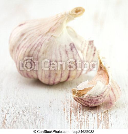 garlic on white wooden background - csp24628032