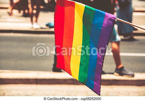 Gay flag on the street background. Big rainbow flag - csp58252000