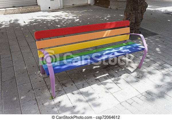 Gay pride rainbow colors painted bench on the street - csp72064612