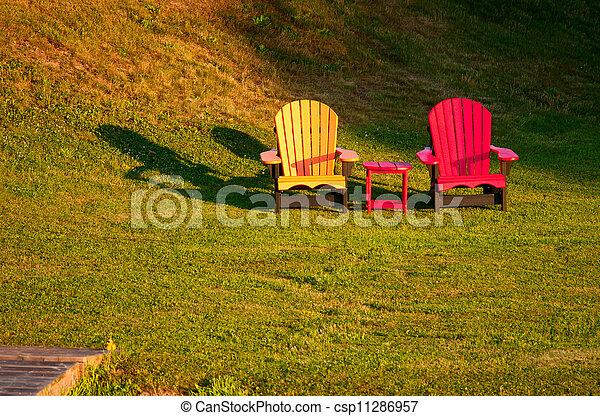 Zwei hell gemalte Stühle auf einem Rasen - csp11286957