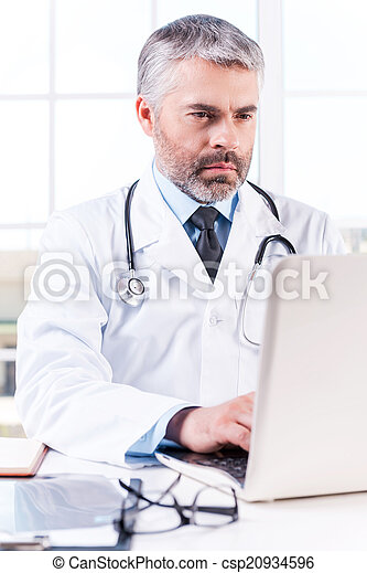 General practitioner. Mature grey hair doctor working on laptop while sitting at his working place - csp20934596