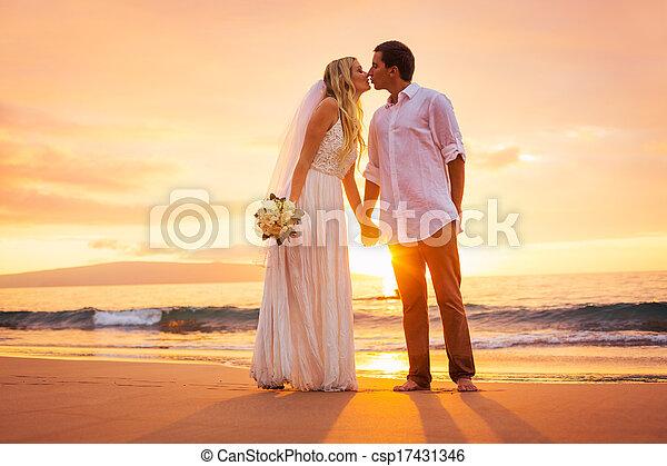 Nur verheiratete Paare, die sich bei Sonnenuntergang am tropischen Strand küssen - csp17431346