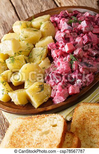 German red herring salad served with boiled potatoes closeup in a plate. vertical - csp78567787