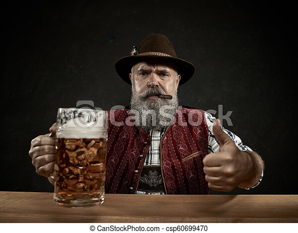 Germany, Bavaria, Upper Bavaria, man with beer dressed in in traditional Austrian or Bavarian costume - csp60699470